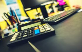 Office and Accounting Concept. Compact Calculator Device on the Accountant Desk.